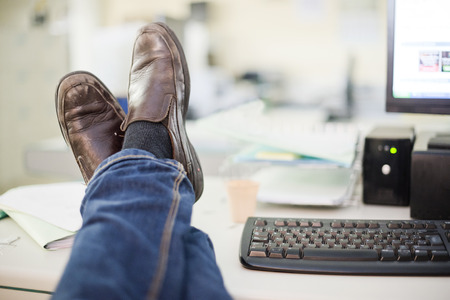 file clerks: Resting at office: human legs on desk Stock Photo