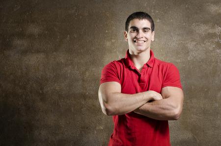 latin man: Strong latin man posing on dirty background smiling Stock Photo