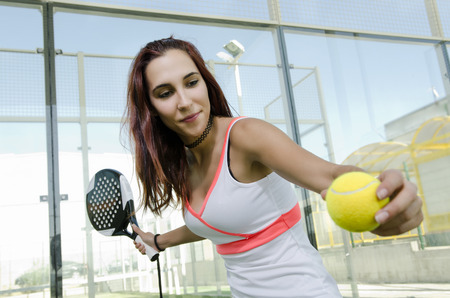Woman ready for paddle tennis serve in real outdoors court photo