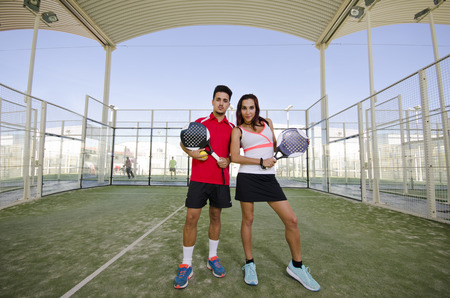 full lenght: Couple in paddle tennis court posing in full lenght portrait