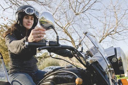 Mujer ocasional en motocicleta con espejo de ajuste Foto de archivo