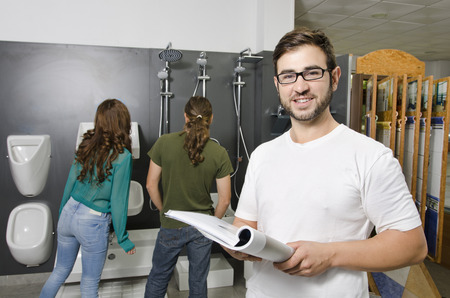 plumbing accessories: Couple at plumbing store choosing wc and sales clerk looking at the view