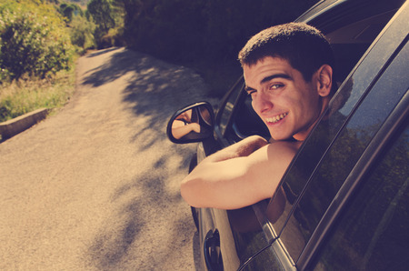 new driver: Young man in black car ready for trip looking at the view