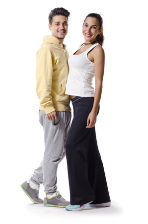 tracksuit: Young couple with sportswear posing isolated on white in full length portrait Stock Photo