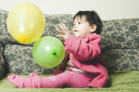 Baby Playing with balloon at home sofa photo