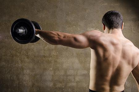 Man lifting weights, back image at old gym. photo