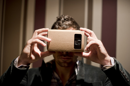 purchased: Man looking his 3-d smartphone with a carton adapter  purchased online Stock Photo