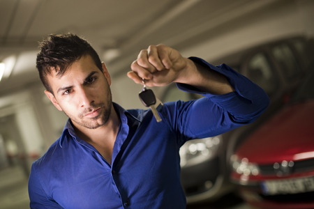 Young man in garage with car keys photo