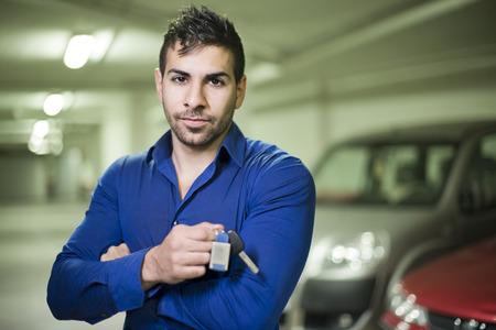 Young posing man with car keys photo