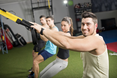People at gym doing trx exercises at crossfit room photo