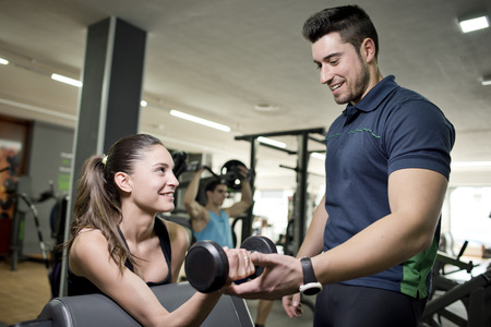 Personal trainer helps girl in gym