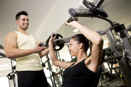 pectoral: Fitness trainer helping woman in pectoral exercises
