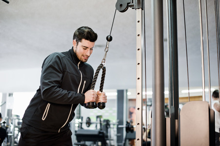 Man training triceps at gym with casual tracksuit