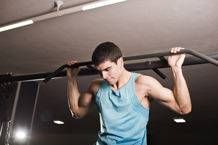 dorsal: Man doing chin exercises at gym, training dorsal muscle