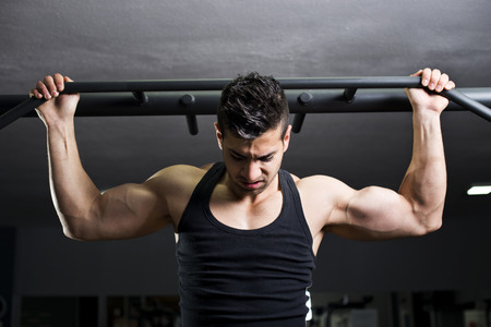 strong chin: Young man at gym training back with dramatic light