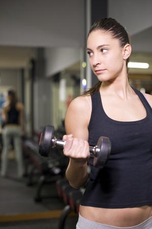 levantar pesas: Mujer de 20 años joven levantando pesas en el gimnasio y la formación que buscan en los ejercicios view.Biceps.