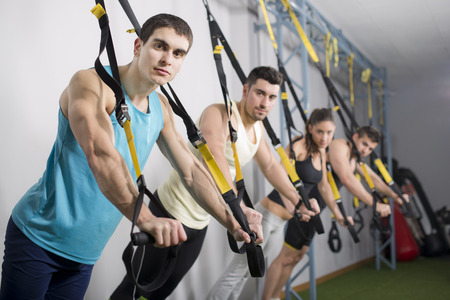 People at gym doing elastic rope exercises at crossfit room photo