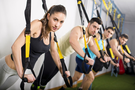 training group: Group of people training in suspension elastic rope at gym and looking at the view