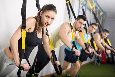 muscle training: Gruppe von Menschen, die Ausbildung in Suspension elastischen Seil zu Fitnessraum und Blick auf die Ansicht