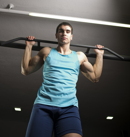 strong chin: Young man training chin and back exercises at gym bar