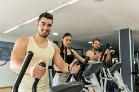 Young people training in eliptical exercises at gym photo