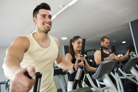 trainers: Active people at gym in elliptical bike, smiling man in focus.
