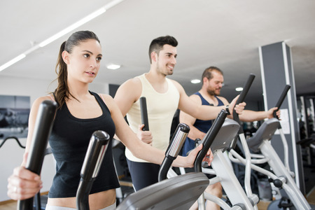 Group with young woman and men on elliptical trainer exercising in gym photo