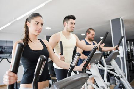 eliptica: Grupo con la mujer joven y el hombre en bicicleta elíptica ejercitan en gimnasia
