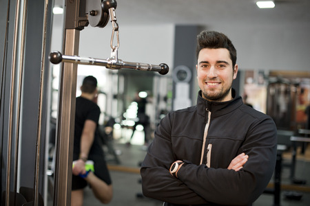 tracksuit: Monitor fitness trainer posing and smiling looking at camera Stock Photo