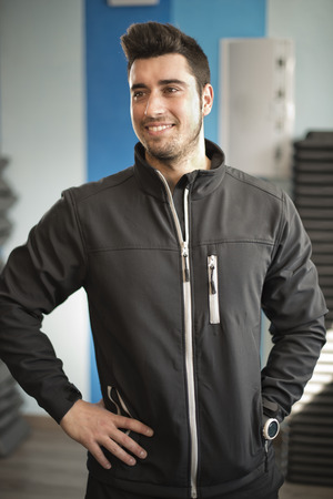 tracksuit: Attractive gym coach posing at fitness room