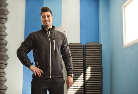 tracksuit: Monitor fitness trainer posing in crossfit room