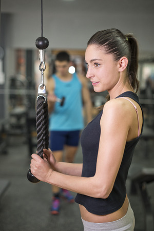 Young woman working triceps exercise at gym photo