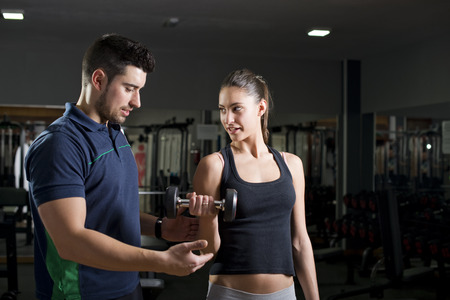 Woman lifting weights at gym training biceps. Personal trainer helps. Focus is in woman.Low key image.