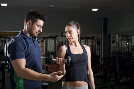 fitness men: Mujer levantando pesas en el b�ceps de capacitaci�n gimnasio. Entrenador personal ayuda. Focus es woman.Low imagen clave. Foto de archivo