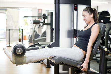 quadriceps: Woman at quadriceps exercise pull machine