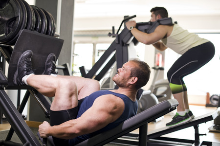 femoral: Two strong men at gym traning legs with press.