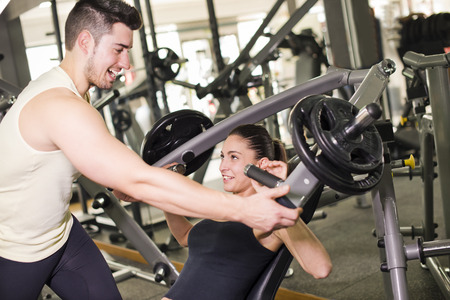 pectoral: Gym coach helping girl doing pectoral exercises with ambient lightning