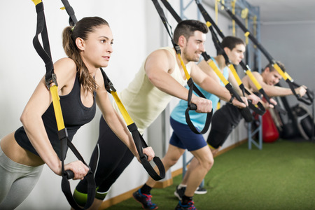 People at gym doing trx exercises at crossfit room