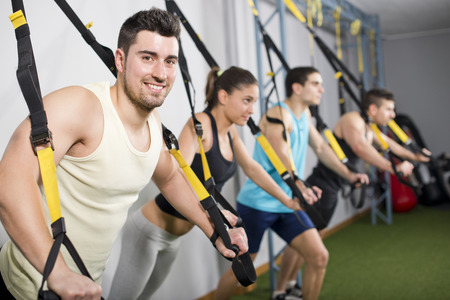 People at gym doing elastic rope exercises at cross and fit room. Man looking at camera smiling photo
