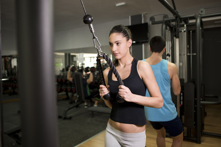 Young woman training triceps at gym near to young man Stock Photo