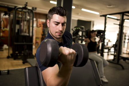 pectoral: Young man training biceps at gym and blurred woman in the background trining pectoral muscle Stock Photo