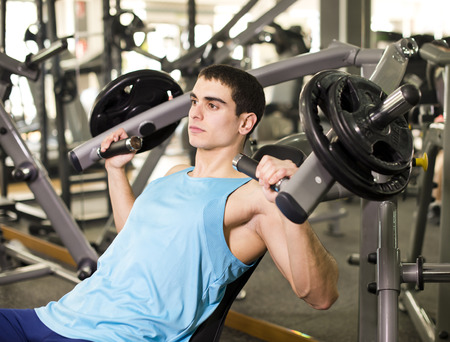 Young attractive latin man lifting weights at gym and training pectoral muscle at dumbbells machine photo