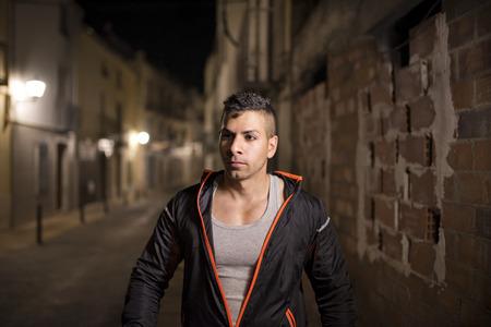 ttractive: Young man in sportswear walking in street. Urban night scenes