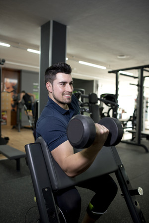 scott: Young smiling and handsome man training biceps at gym