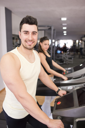 Young smiling man in treadmill ready for run. Woman in background photo