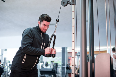 tracksuit: Young athlete training triceps at gym with tracksuit