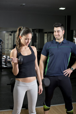 Woman lifting weights near to personal trainer at gym photo