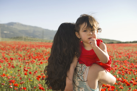 Mother carrying baby daughter at outdoors in spring image at poppies field photo