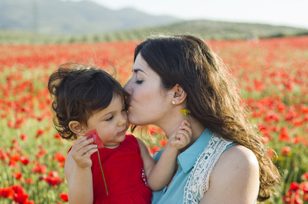 Mother kissing baby at poppies field in spring day photo