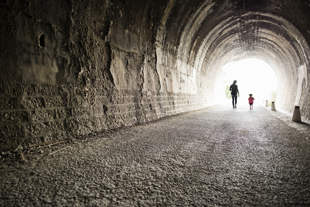 light at the end of the tunnel: Back tunnel image, mother and daughter in light with wide anle lens Stock Photo